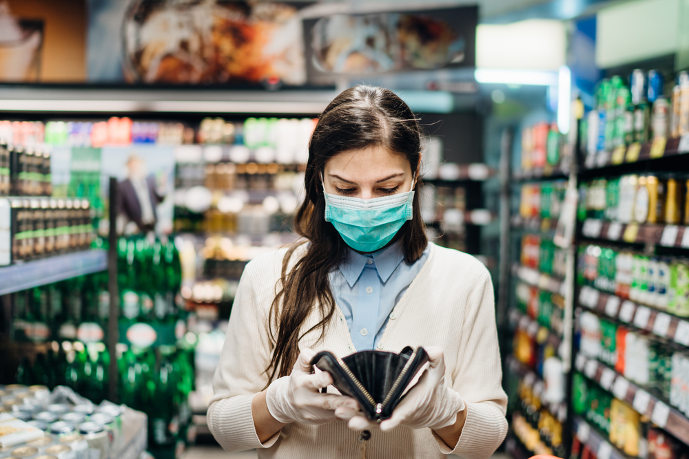 woman checking wallet while shopping and wearing ppe