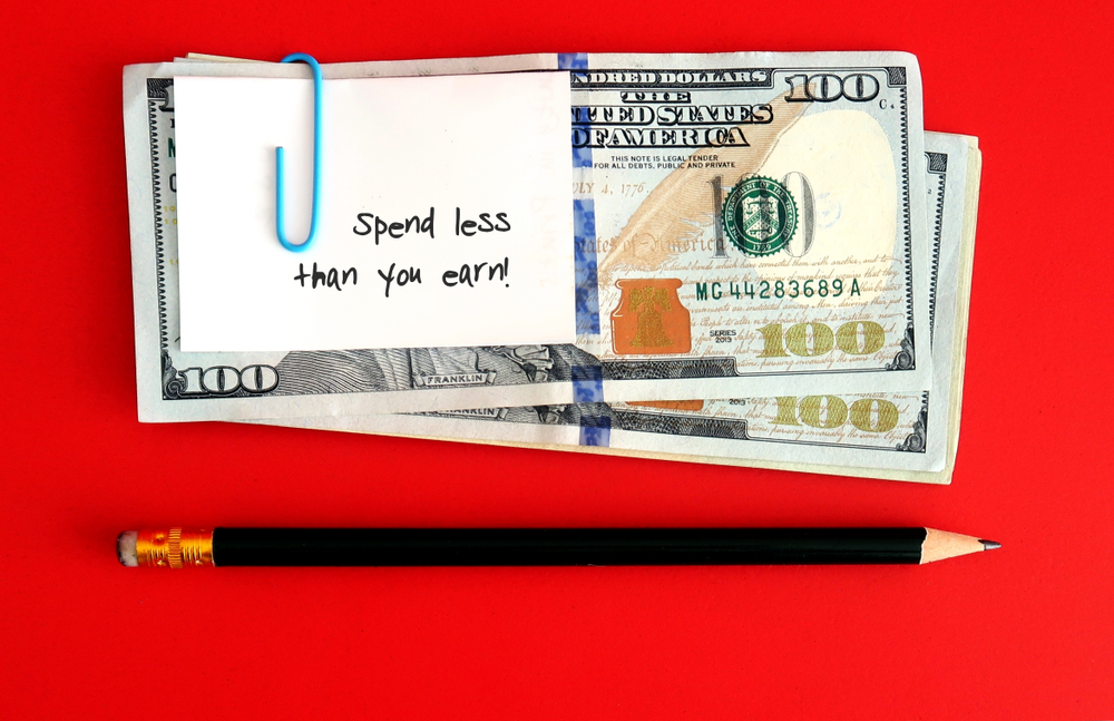 spend less than you earn note paper clipped to bills
